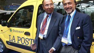 Serge Dassault (à gauche) et son fils Olivier, le 4 avril 2005 au Forum Grimaldi de Monaco, devant une voiture électrique du groupe. (JACQUES MUNCH / AFP)
