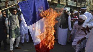 Des manifestants musulmans brûlent un drapeau français à Karachi, au Pakistan, le 30 octobre 2020. (ASIF HASSAN / AFP)