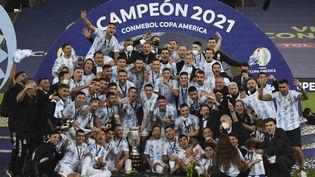 Les Argentins célèbrent sur le podium leur trophée après avoir remporté la finale de la Copa America face au Brésil au stade Maracana à Rio de Janeiro, le 10 juillet 2021. (CARL DE SOUZA / AFP)