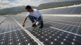 Une personne travaille sur le toit d'une entreprise où une centrale photovoltaïque a été installée,au Port, sur l'île de la Réunion, le 18 septembre 2008. (RICHARD BOUHET / AFP)