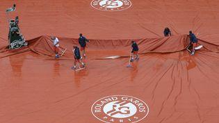 Un court de Roland-Garros bâché, sous la pluie, le 22 mai 2016. (PASCAL ROSSIGNOL / REUTERS)
