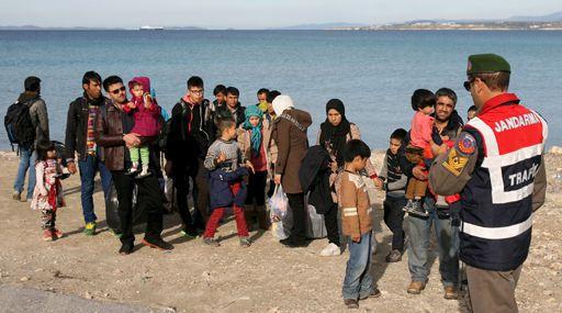 Un gendarme turc prend en charge un groupe de réfugiés à Cesme (ouest de la Turquie) pour les conduire à des bus le 1er décembre 2015. Il s'agit de les empêcher de s'embarquer pour l'île grecque de Chios et de pouvoir ainsi arriver sur le territoire de l'UE. (REUTERS - Denizhan Guzel)