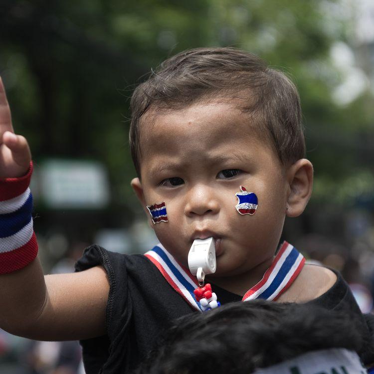 Un enfant est assis sur les épaules d'un manifestant antigouvernement, dans un rassemblement à Bangkok (Thaïlande), le 2 avril 2014. (NICOLAS ASFOURI / AFP)