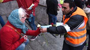 Un réfugié syrien offre des fleurs aux passants,en guise de manifestationcontre les violences du Nouvel An, à Cologne (Allemagne), le 16 janvier 2016. (PATRIK STOLLARZ / AFP)