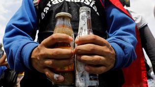 Un manifestant anti-Maduro tient des bouteilles remplies de matières fécales, à Caracas (Venezuela), mercredi 10 mai 2017. (CARLOS GARCIA RAWLINS)