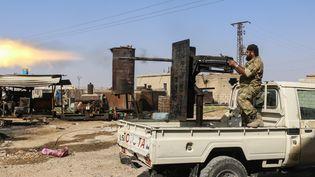 Un soldat de l'Armée nationale syrienne tire en direction de Ras al-Ayn (Syrie), le 13 octobre 2019. (HUSEYIN NASIR / ANADOLU AGENCY / AFP)