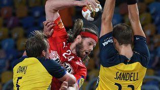 Mikkel Hansen passe en force entre deux Suédois lors de la finale du Mondial le 31 janvier 2021 (ANNE-CHRISTINE POUJOULAT / AFP)