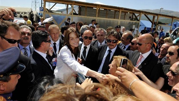 Carla Bruni-Sarkozy lors de sa visite dans un quartier de la ville d'Aquila, ravagé par un séisme le 6 avril 2009 (© AFP PHOTO / POOL / PHILIPPE WOJAZER)