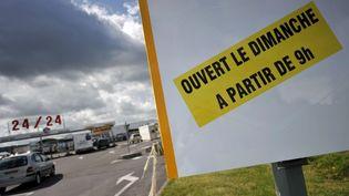 Un panneau indique l'ouverture d'un magasin le dimanche sur le parkingd'un supermarché à Cabourg (Calvados), le 24 juillet 2009. (MYCHELE DANIAU / AFP)