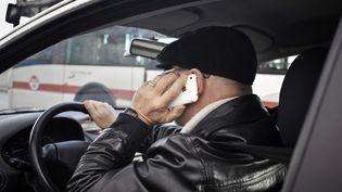 Téléphoner en voiture avec son appareil en main, comme ce conducteur photographié à Lyon le 4 janvier 2012, était déjà passible d'une contravention. Il sera interdit à partir du 1er juillet d'avoir des oreillettes ou un kit mains libres. (JEAN-PHILIPPE KSIAZEK / AFP)