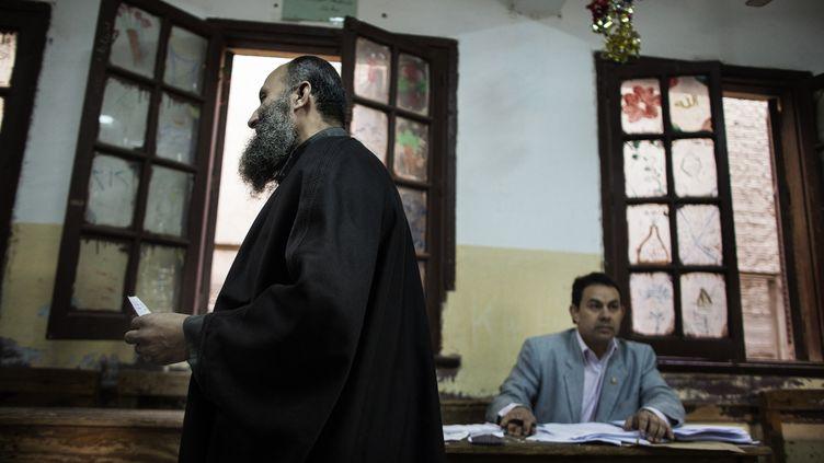 Un homme en train de voter à l'occasion du référendum sur la constitution, au Caire en Egypte, le 15 décembre 2012. (MARCO LONGARI / AFP)