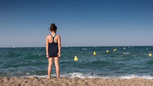 Une jeune fille trempe ses pieds dans la Méditerranée, le 30 juin 2019, à Argelès-sur-Mer (Pyrénées-Orientales). (LIONEL PEDRAZA / HANS LUCAS / AFP)