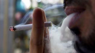 Un homme fume une cigarette (illustration). (FAYEZ NURELDINE / AFP)