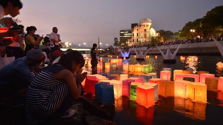 Des personnes se recueillent devant le Dôme de Genbaku, le mémorial de la paix d'Hiroshima (Japon) pour commémorer le 70e anniversaire du premier bombardement atomique de l'histoire,le 6 août 2015. (KAZUHIRO NOGI / AFP)