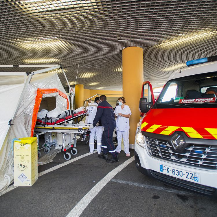 Un malade du Covid-19 sur un brancard est installé dans une tente de triage des patients devant le CHU de Fort-de-France, en Martinique, le 30 juillet 2021. (LIONEL CHAMOISEAU / AFP)