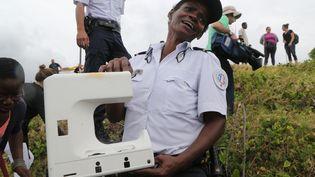 Une policière montre un débris trouvé sur le bord de mer à Saint-Denis, à la Réunion, le 4 août 2015. (RICHARD BOUHET / AFP)