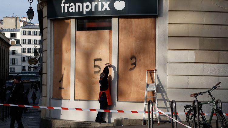 Un employé d'un supermarchéinstalle des panneaux en bois sur sa devanture, le 17 décembre 2019, à Paris. (FRANCOIS GUILLOT / AFP)