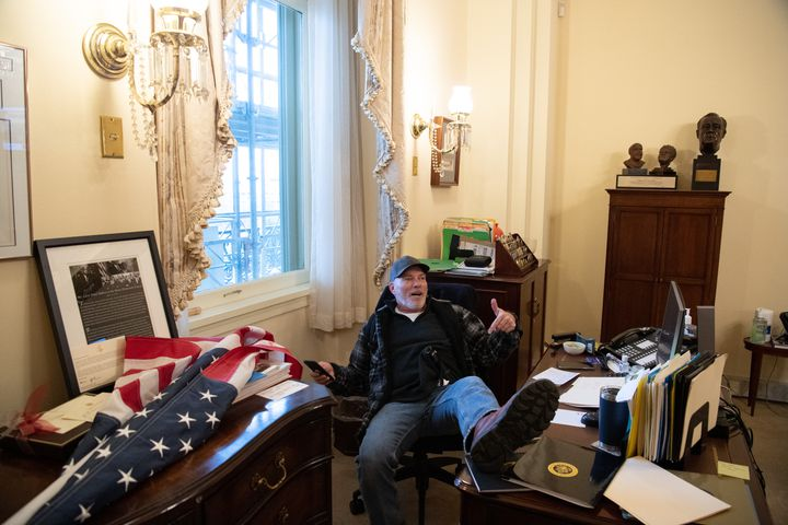 Richard Barnett, originaire de l'Arkansas, pose dans le bureau de la présidente de la Chambre des représentants, Nancy Pelosi, mercredi 6 janvier 2021, à Washington. (SAUL LOEB / AFP)