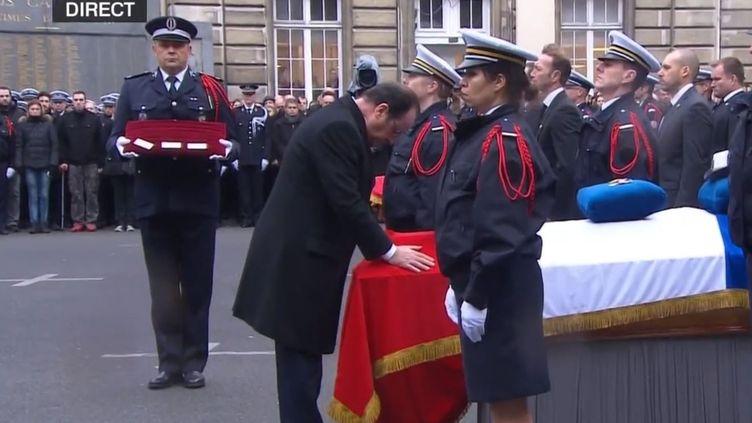 Le président de la République, François Hollande, s'incline devant les cercueils des policiers tués durant les attentats, lors d'une cérémonie d'hommage à la préfecture de Police de Paris, le 13 janvier 2015. (FRANCE 2 / FRANCETV INFO)