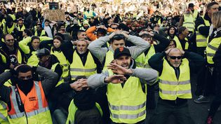 """Des """"gilets jaunes"""" à genoux à Marseille (Bouches-du-Rhône) lors de la manifestation le 8 décembre 2018. (THEO GIACOMETTI / HANS LUCAS / AFP)"""