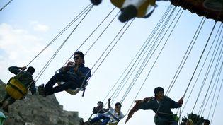 Des jeunes Afghans s'amusent dans un manège à l'occasion des vacances de l'Eid al-Fitr, à Kaboul, le 17 juillet 2015. (WAKIL KOHSAR / AFP)