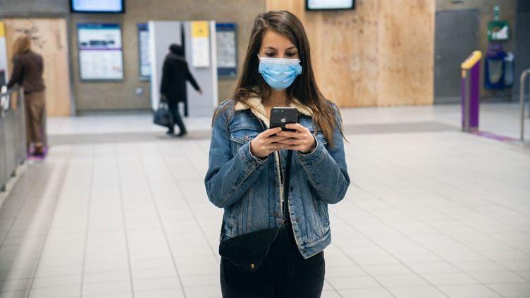 Une femme utilise son téléphone portable, à Rennes (Ille-et-Vilaine), en avril 2020. (VALENTIN BELLEVILLE / HANS LUCAS / AFP)
