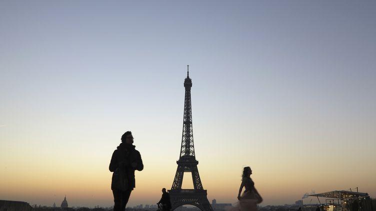 Des passants circulent devant la tour Eiffel, sur la place du Trocadéro, le 20 janvier 2017. (LUDOVIC MARIN / AFP)