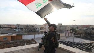 Un soldat des forces spéciales soulève l'étendart irakien sur un bâtimentde la ville deBartella, à 15km de Mossoul, le 21 octobre 2016 (GORAN TOMASEVIC / REUTERS)
