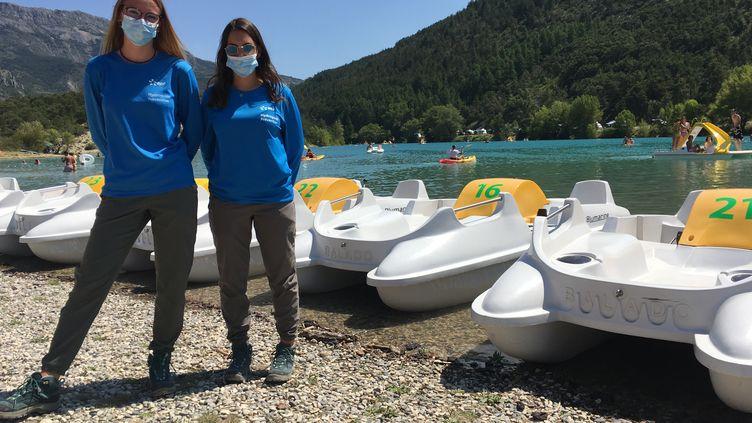 Amandine et Pauline, étudiantes et hydroguides d'EDF, alertent les touristes sur les risques de baignade ou de paddle trop près du barrage du lac de Castillon, dans les Alpes-de-Haute-Provence. (GREGOIRE LECALOT / RADIO FRANCE)