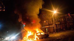 Deux voitures brûlent à Baltimore (Maryland) le 27 avril 2015 lors d'émeutes ayant suivi les obsèques d'un jeune Noir, décédé une semaine après son interpellation par la police. (ANDREW BURTON / GETTY IMAGES NORTH AMERICA)