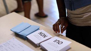 Une femme vote dans un bureau de Nouméa lors du référendum concernant l'indépendance de la Nouvelle-Calédonie, dimanche 4 novembre 2018. (THEO ROUBY / AFP)