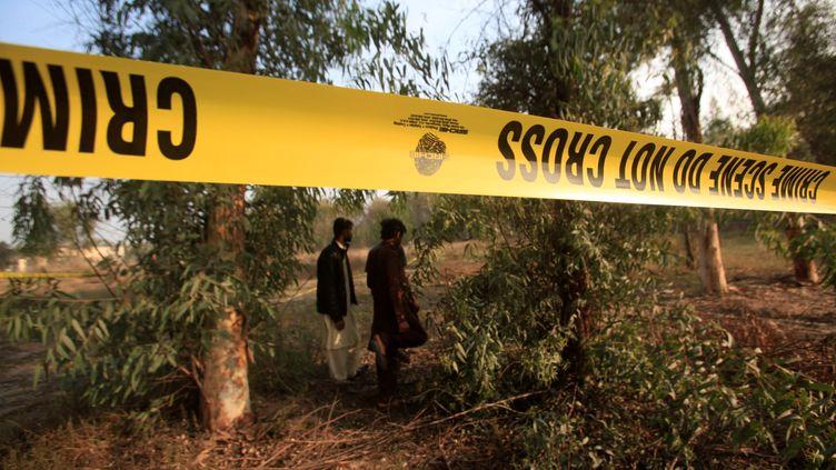 Deux hommesdans la zone où l'adolescent a été dévoré par les lions, le 26 février 2020, à Lahore (Pakistan). (MOHSIN RAZA / AFP)