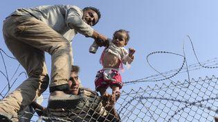 Passage de réfugiés à la frontière turco-syrienne en juin 2015  (BULENT KILIC / AFP)