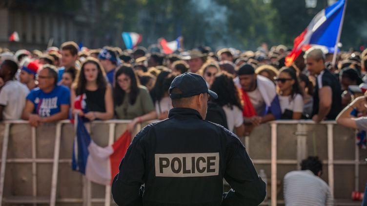 Un policieren faction à proximité de supporters français, à l'Hôtel de Ville à Paris, le 10 juillet 2018. (AURELIEN MORISSARD / MAXPPP)