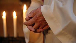 Un prêtre prie devant des cierges (mars 2017). (VANESSA MEYER / MAXPPP)