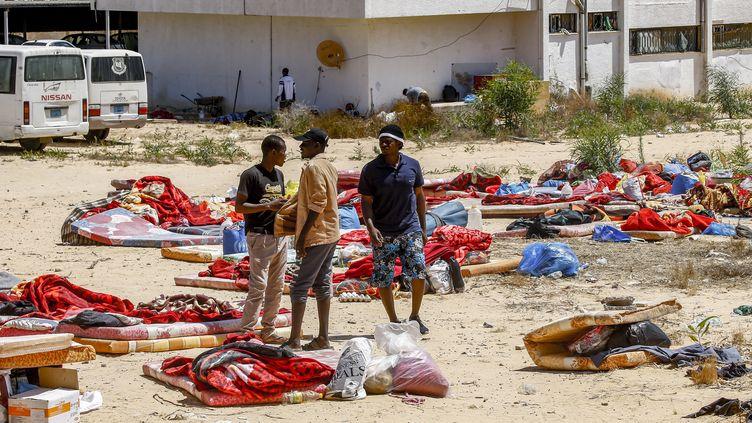 Des migrants à l'extérieur du centre de détention de Tajoura, dans la banlieue de Tripoli, le 3 juillet 2019. (MAHMUD TURKIA / AFP)