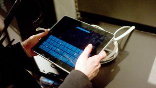 Une personne utilise une tablette numérique dans un magasin de matériel informatique à Paris, le 26 janvier 2011. (MARTIN BUREAU / AFP)