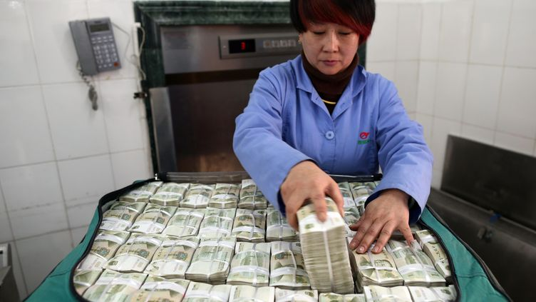 Chinoise empaquetant des Yuans au centre de transport de Kunming (WANG YUHENG / IMAGINECHINA)