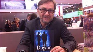 """Marc Dugain avec son roman """"Quinquennat"""", sur le stand Gallimard au Salon du Livre. (ANNE BRIGAUDEAU / FRANCE TV INFO)"""