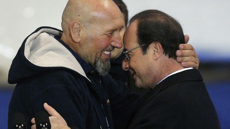 Serge Lazarevic et François Hollande sur le tarmac de l'aéroport militaire de Villacoublay (Yvelines) le 10 décembre 2014. (CHRISTOPHE ENA / AP / SIPA)