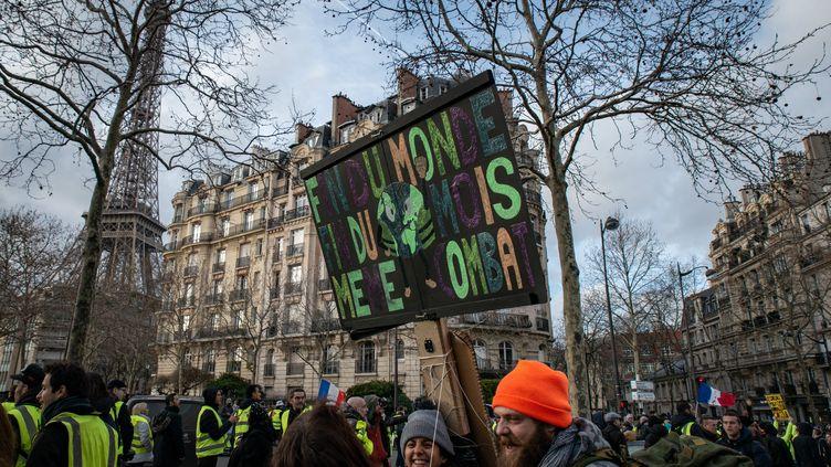 """Camelia, au centre avec un bonnet gris, sous sa pancarte """"Fin du monde, fin du mois, même combat"""", dans une manifestation de """"gilets jaunes"""", à Paris, le 9 février 2019. (CHRISTOPH DE BARRY / HANS LUCAS / AFP)"""