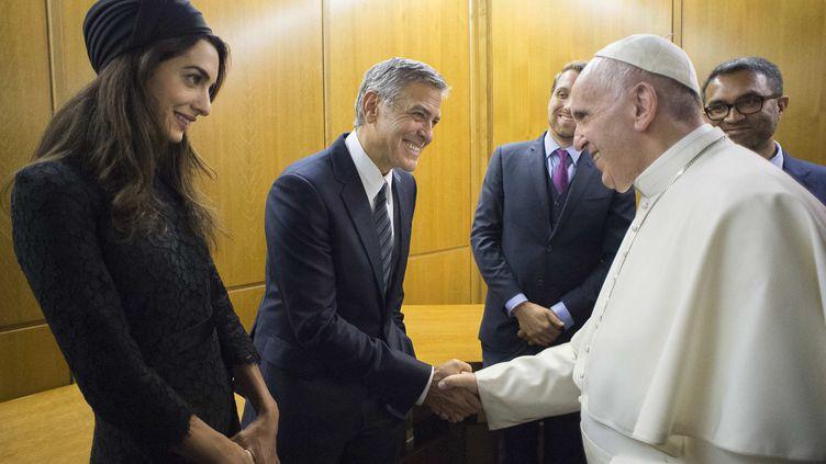 Le papeFrançois serre la main de l'acteur américain George Clooney et deson épouse Amal Clooney, le 29 mai 2016. (OSSERVATORE ROMANO / AFP)