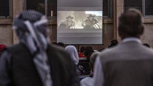 Des spectateurs se rassemblent dans devant un écran de cinéma disposé dans une cour d'école du village de Shaghir Bazar, au Nord-Est de la Syrie. (DELIL SOULEIMAN / AFP)