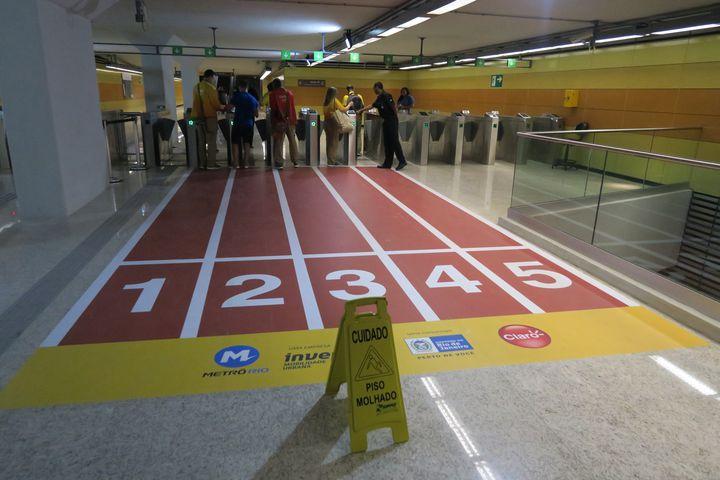 """Une pancarte indique """"attention, sol glissant"""", devant une fausse piste d'athlétisme disposée dans la ligne 4 du métro de Rio de Janeiro (Brésil), le 4 août 2016. (PIERRE GODON / FRANCETV INFO)"""