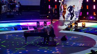 Le chanteur Gilbert Montagné au piano, Laury Thilleman et Garou en arrière plan, à Roland Garros le 21 juin 2021. (JEREMIE LAURENT-KAYSEN)