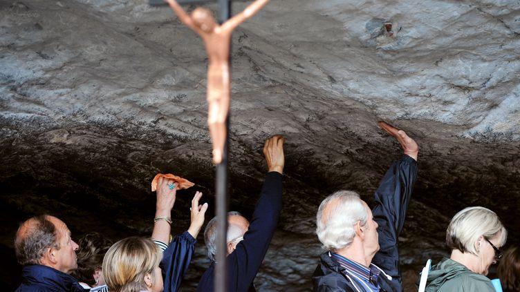 Des pélerins touchent la pierre de la grotte de Massabielle lors de la fête de l'Assomption à Lourdes, le 15 août 2008. (PASCAL PAVANI / AFP)