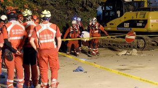 Des secouristes de la Croix-Rouge italienne transporte le corps d'une victime du séisme le 26 août 2016 à Amatrice (Italie). (ANDREAS SOLARO / AFP)