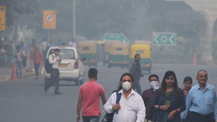 Des habitants de New Delhi portent des masques pour se protéger de la pollution. (DOMINIQUE FAGET / AFP)
