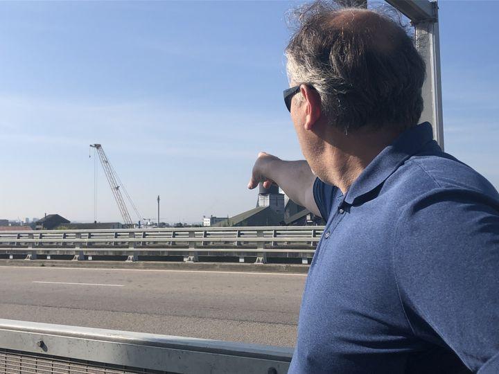 Pierre-Emmanuel Brunet, président de l'association Rouen Respire, montre le siège de l'entreprise Lubrizol, à Rouen (Seine-Maritime), le 24 septembre 2021. (LOUISA BENCHABANE / FRANCEINFO)