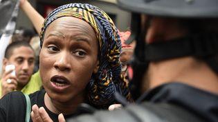 La soeur d'Adama Traoré, Assa Traoré, parle avec un policier lors d'une marche de protestation à la mémoire de son frère, devant la Gare du Nord à Paris, le 30 juillet. (DOMINIQUE FAGET / AFP)